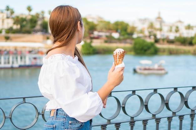 Feliz niña de espaldas comiendo un helado en verano en españa disfrutando de la vista del río