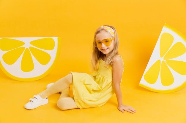 Feliz niña con gafas de sol posando con rodajas de limón decoraciones