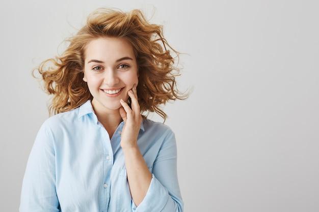 Feliz niña hermosa y soñadora con pelo corto y rizado sonriendo