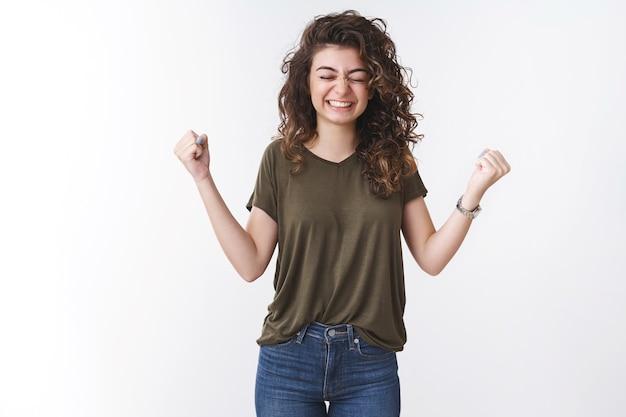 Feliz niña hizo realidad el sueño apriete los puños con alegría celebrando la victoria sonriendo decir sí cerrar los ojos felizmente lograr la meta lograr recibir buenas noticias positivas, triunfar fondo blanco