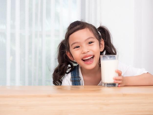 Feliz niña linda de 6 años bebiendo leche de vidrio.