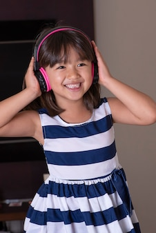 Feliz niña linda escuchando música
