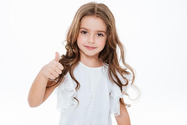 Feliz niña linda de pie y mostrando los pulgares para arriba