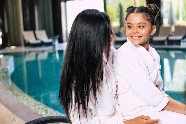 Feliz niña linda con su madre en albornoces están felices juntos mientras están sentados en el salón de spa