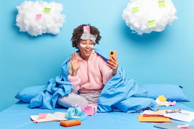 Feliz niña milenaria con ondas de cabello afro hola en el dispositivo del teléfono inteligente hace investigación o asignación en casa disfruta de un ambiente doméstico