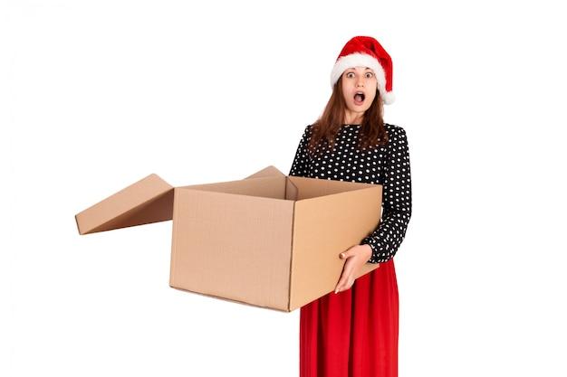 Feliz niña morena con sombrero de navidad con caja abierta