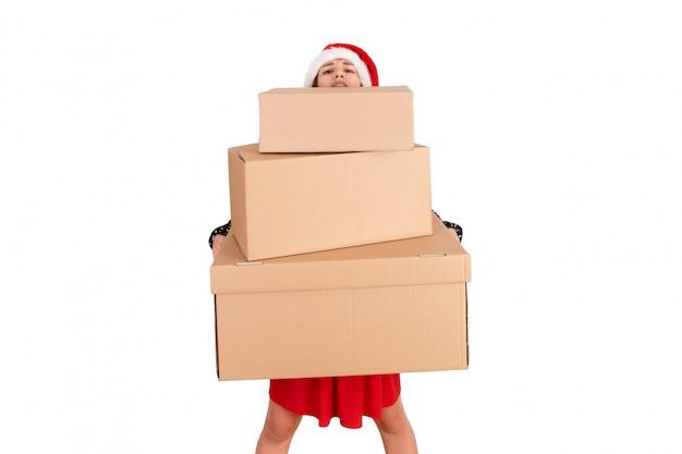 Feliz niña morena con sombrero de navidad con cajas