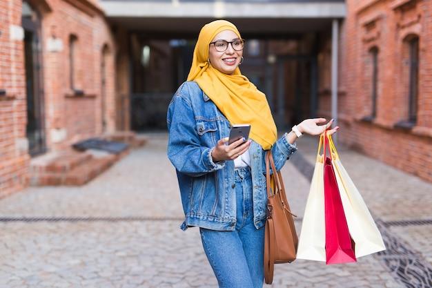 Feliz niña musulmana árabe con bolsas de la compra.
