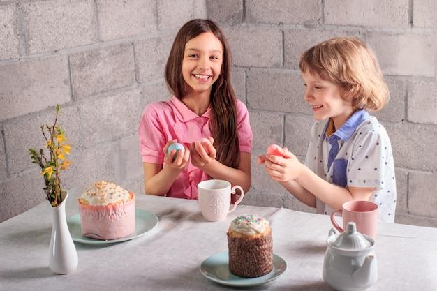 Feliz niña y niño jugando el tradicional juego de pascua - golpeteo de huevos con huevos de colores en casa