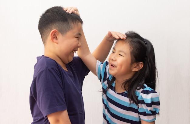 Feliz niña y niño midiendo su altura