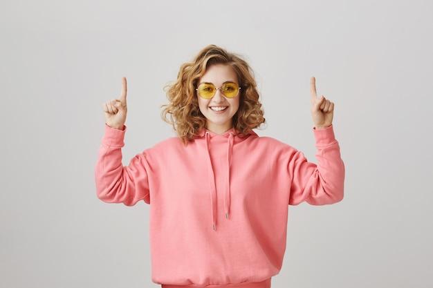 Feliz niña de pelo rizado satisfecha con gafas de sol apuntando con el dedo hacia arriba