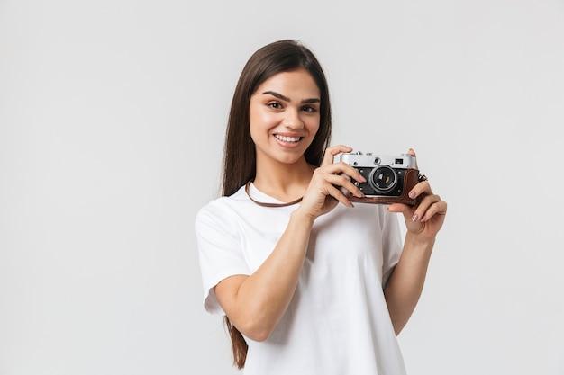 Feliz niña de pie aislado en blanco, sosteniendo la cámara de fotos