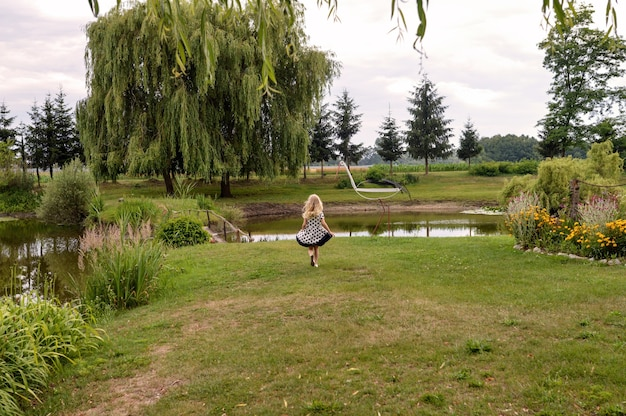 Feliz niña de pie delante de un estanque en el hermoso jardín