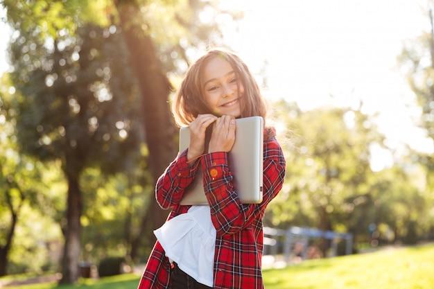 Feliz niña de pie en el parque mientras abraza a su computadora portátil