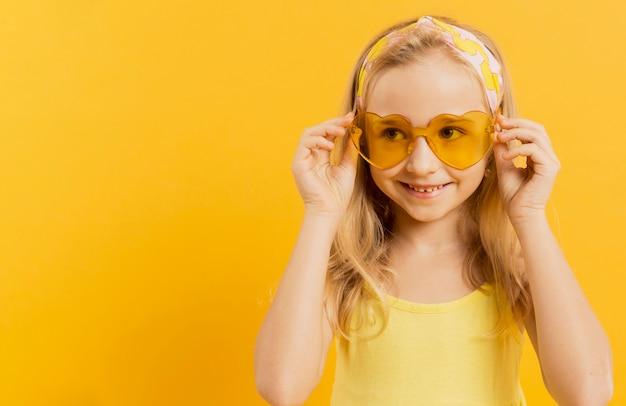 Feliz niña posando con gafas de sol