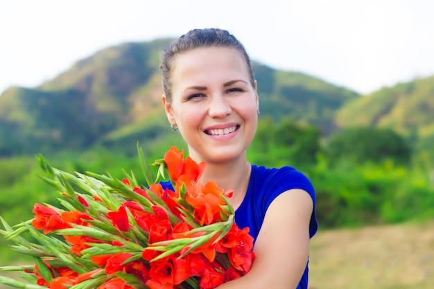Feliz niña positiva alegre, joven muy bonita mujer sonriendo, riendo con regalo de vacaciones, gran ramo rojo hermoso de gladiolos, gladiolos. primavera, 8 de marzo concepto del día internacional de la mujer