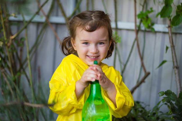 Feliz niña riendo rocía plantas en el jardín