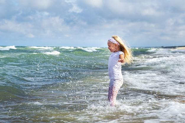 Feliz niña en ropa en la playa del mar báltico en el asador de curlandia en lituania
