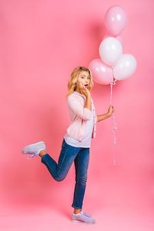 Feliz niña rubia con globos celebrando las fiestas