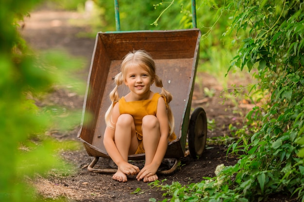 Feliz niña rubia en el país en un jardín carretilla sentado sonriendo
