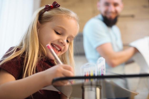 Feliz niña rubia sonriendo mientras dibuja en la cocina por la mañana mientras su padre lava los platos.