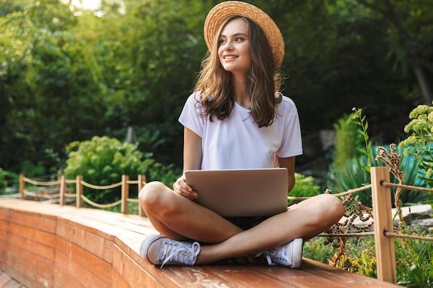 Feliz niña sentada con ordenador portátil en el parque al aire libre