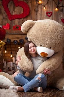 Feliz niña sentada con oso de peluche en el ambiente de san valentín