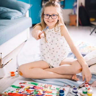 Feliz niña sentada en el piso con pincel
