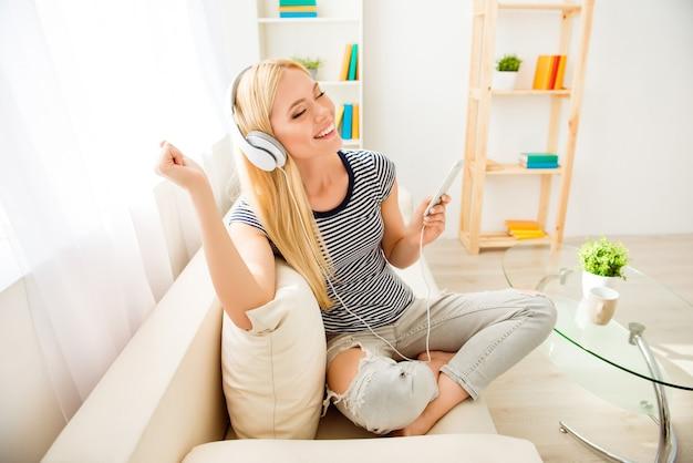 Feliz niña sentada en el sofá, escuchando música y bailando
