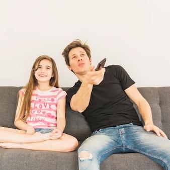 Feliz niña sentada en el sofá con su padre con control remoto en la mano