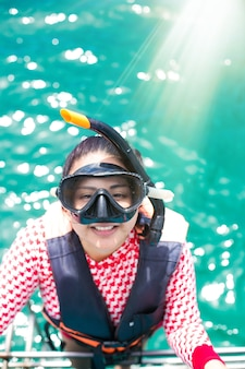 Feliz niña de snorkel divirtiéndose en el agua del océano snorkel en vacaciones caribeñas en tailandia