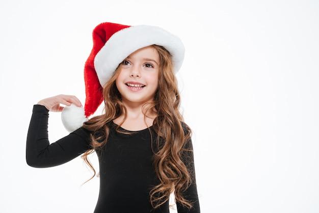 Feliz niña con sombrero de santa claus de pie y sonriente