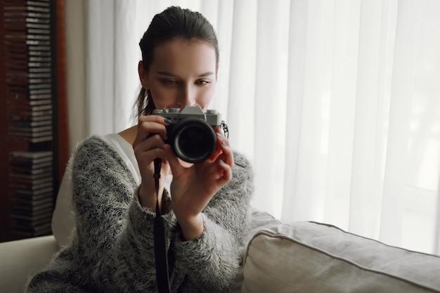 Feliz niña sonriente con cámara de fotos y teléfono en sus manos en el sofá junto a la ventana