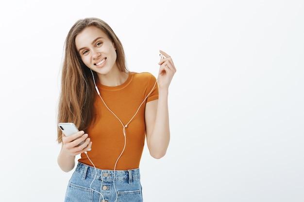 Feliz niña sonriente despegar auriculares y mirar, escuchar podcast o música en el teléfono móvil