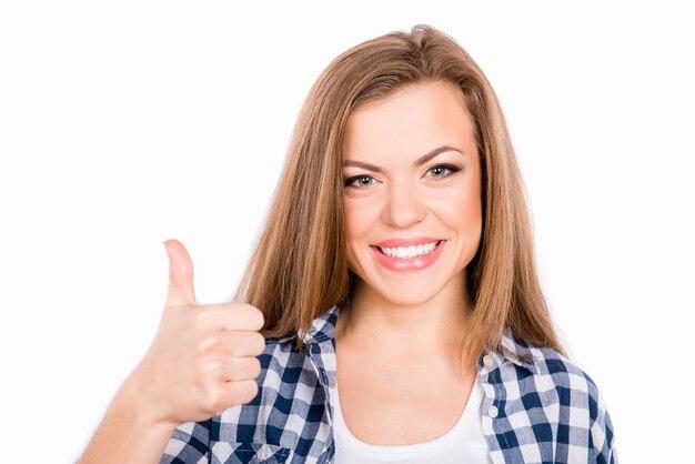 Feliz niña sonriente joven gesticulando y mostrando el pulgar hacia arriba