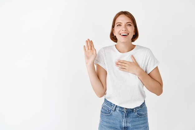 Feliz niña sonriente levantando el brazo y poniendo la mano en el corazón, siendo honesto, diciendo la verdad, juro ser sincero, de pie contra la pared blanca