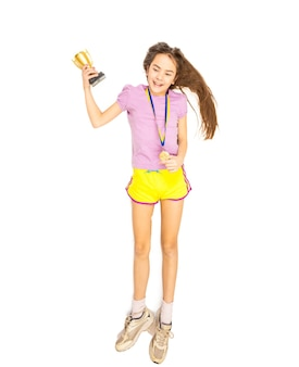 Feliz niña sonriente posando con copa y medalla de oro. disparo aislado en el suelo.