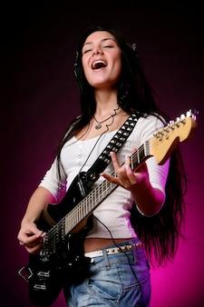 Feliz niña sonriente tocando la guitarra
