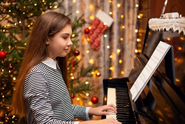 Feliz niña sonriente tocando el piano con adornos brillantes en el fondo