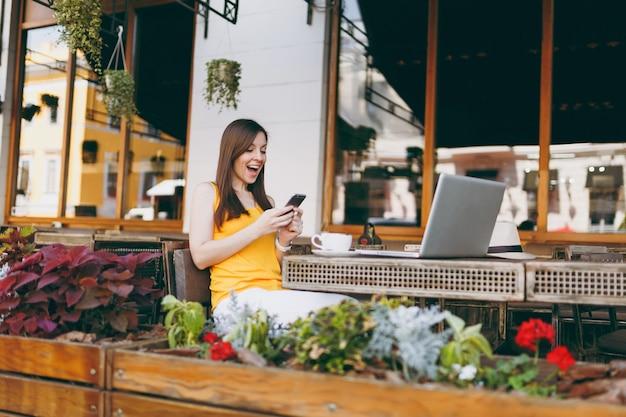 Feliz niña sorprendida en la cafetería de la calle al aire libre sentado en la mesa con la computadora portátil, mensaje de texto en un amigo del teléfono móvil, en el restaurante durante el tiempo libre