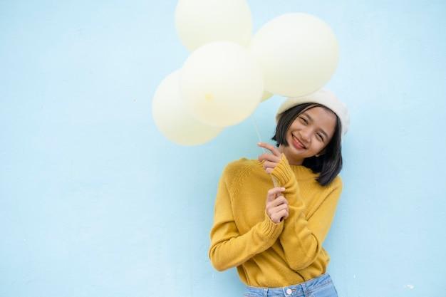 Feliz niña sostenga globos amarillos sobre fondo azul.
