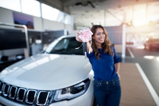 Feliz niña sosteniendo las llaves de su nuevo suv en la sala de exposición del concesionario de automóviles
