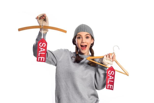 Feliz niña sosteniendo percha con precio de venta, aislado en blanco