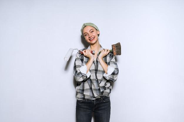 Feliz niña sosteniendo un rodillo y un pincel para pintar las paredes de su nuevo apartamento