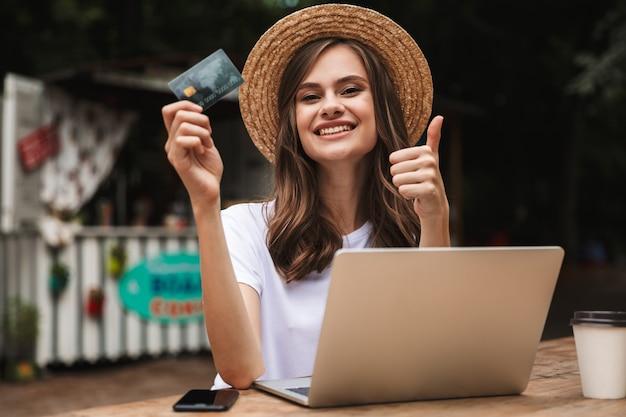Feliz niña sosteniendo una tarjeta de crédito de plástico mientras está sentado con una computadora portátil y un café en el café al aire libre, mostrando los pulgares para arriba