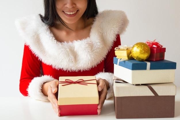 Feliz niña en traje de santa decorando regalos de navidad