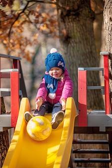 Feliz niña de tres años en la chaqueta en el tobogán en el parque