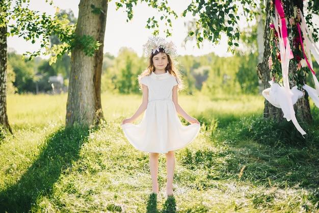 Feliz niña con un vestido con una corona de flores en la cabeza de flores en el campo