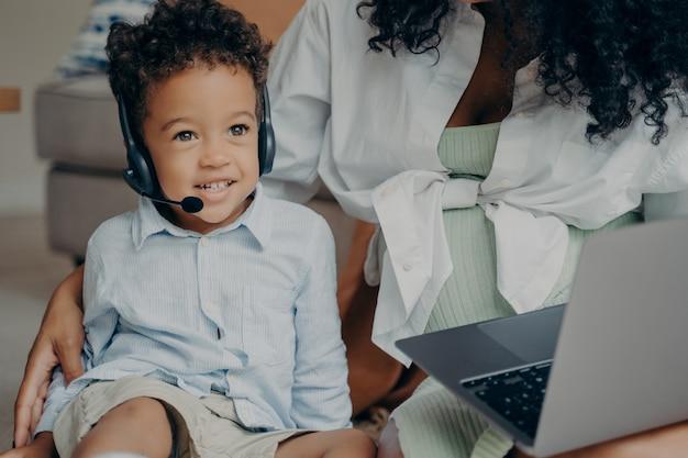 Feliz niño afroamericano hablando con su familia a través de la webcam en la computadora portátil con la ayuda de las madres