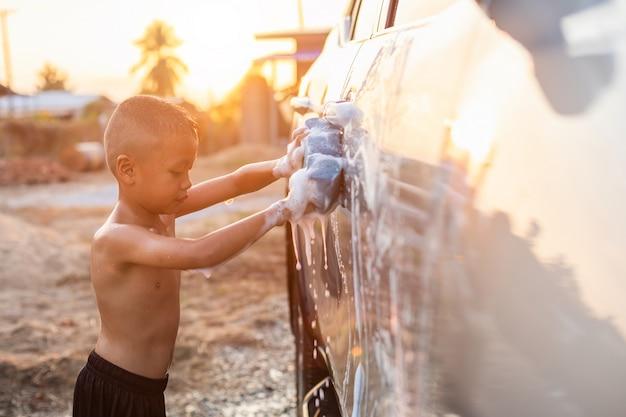 Feliz niño asiático con jabón blanco y el uso de una esponja azul para lavar el automóvil al aire libre en la hora del atardecer